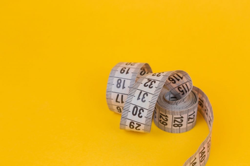 White measuring tape on a yellow background. Diet. Slimming. Obesity. Place for an inscription. Weight loss marathon. Advertising. Top view. The close plan.
